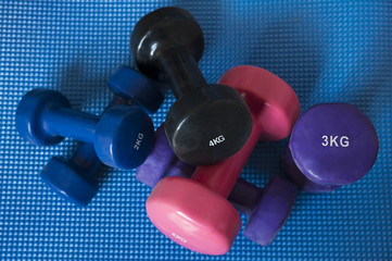 A pile of neoprene coated iron dumbbells of different weights, used for muscle toning, aerobic and weight training, positioned on a blue mat, part of fitness classes and at-home workout routine