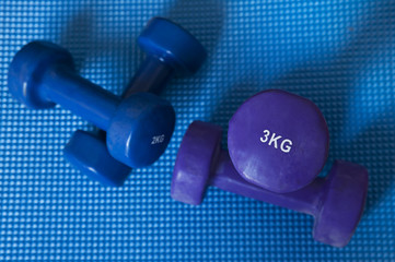 Neoprene coated iron dumbbells, a pair of 3 kg and a pair of 2 kg, used for muscle toning, aerobic and weight training, positioned on a blue mat, part of fitness classes and at-home workout routine