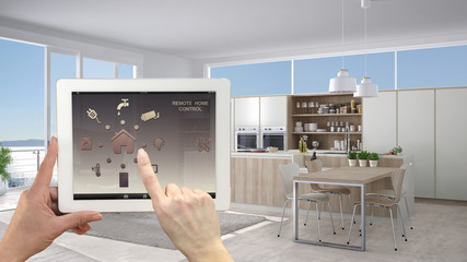 Smart remote home control system on a digital tablet. Device with app icons. Interior of minimalist white kitchen in the background, architecture design.