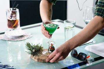 Barman put the martini glass with Christmas green alcoholic cocktail at the bar counter