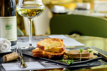 Tasty foie Gras with toasts and glass of white wine at a restaurant