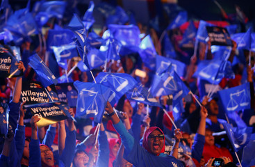 Supporters of Malaysia's ruling party National Front waves the party flags during the launch of its manifesto for the upcoming general elections in Kuala Lumpur