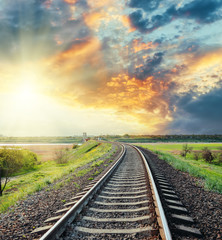 railroad to horizon in colored sunset