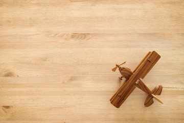 top view photo of toy airplane over wooden background.