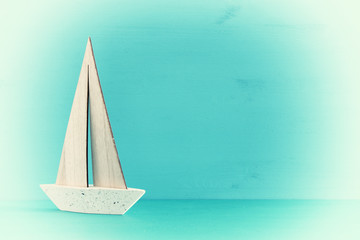 nautical concept with white decorative sail boat over blue wooden table and background.