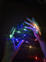 Garland of colorful lights in hands on a dark background