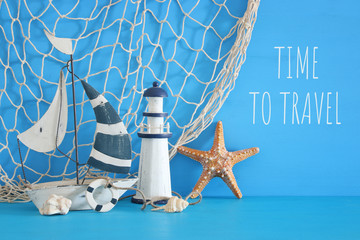 nautical concept with white decorative sail boat, lighthouse, starfish, seashells and fishnet over blue wooden table and background.