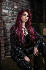 redhead adult girl biker in the leather wear indoor