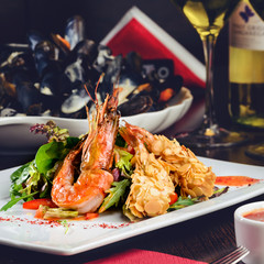 Romantic dinner at a restaurant. Delicious prepared shrimp with tomatoes, sauce and basil leaves, toned image