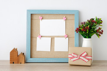 Blank paper cards hanging on blue vintage wooden frame and gift box on table background, copy space for text, aniversary, happy birthday and invitation card
