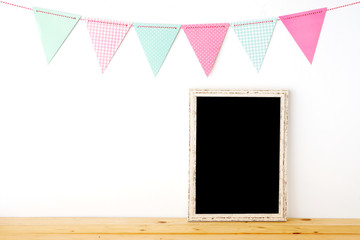Colorful party flags hanging over blank white vintage wooden frame on wood table background, birthday, anniversary, celebrate event, festival background