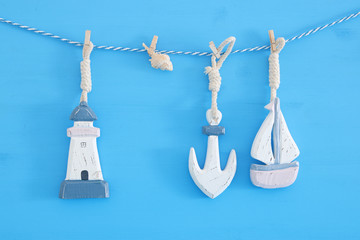 nautical concept with sea lifestyle decorations: sail boat and anchor hanging on a string over blue wooden background.