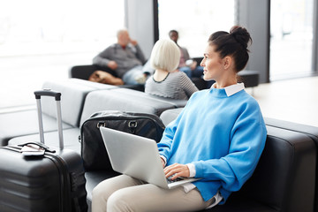 Young businesswoman in blue pullover sitting in airport lounge and working in the net while waiting for flight