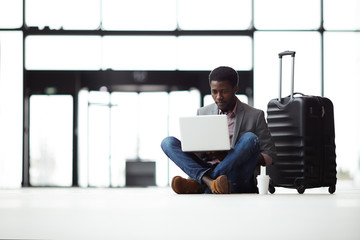 Cross-legged businessman with laptop sitting on the floor in airport lounge with suitcase near by and watching online video or chatting to someone