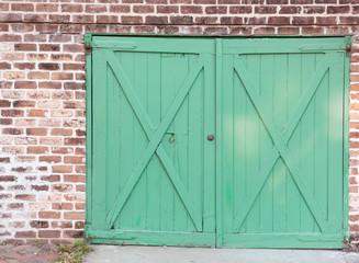Green doors on a brick wall