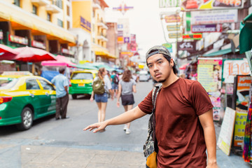 Portrait of handsome young man standing on the city street and hailing a taxi at Khao San Road, Bangkok, Thailand