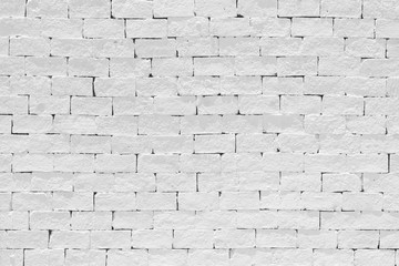 Old aged rough brick wall texture background painted in white color in grunge style .
