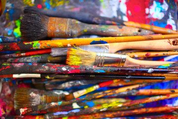 Paint brushes of different sizes, stained by vivid colors, close-up
