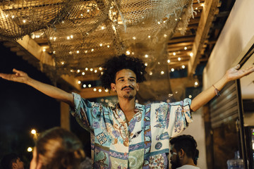 Indian ethnicity afro hair DJ raise his hands to invite people to dance at tropical party in the caribbean sea in Santa Marta, Colombia