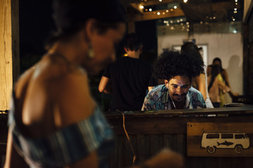 Indian ethnicity with afro hair DJ controlling equipment and people dancing in a tropical party in the caribbean in Santa Marta, Colombia