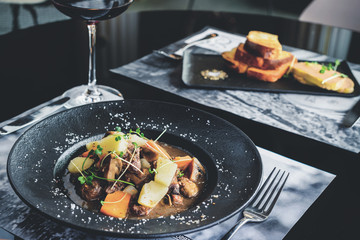 Romantic dinner in the resraurant. Two appetizing dishes and glass of red wine, toned image