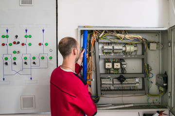 The installer is laying the cable in an electrical box. The electrician performs the work in the electrical room. Man is checks the operation of the electricity supply system
