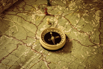 Retro compass is on top of the old tourist map with drawing pin. The arrow of the compass indicates the route of movement of tourists. The northern direction.