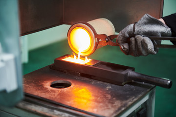 Melting gold. Molted metal pouring into bar form