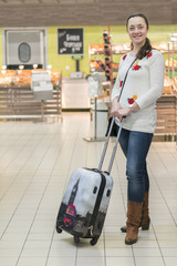 A middle-aged woman with a suitcase in a supermarket