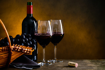 Still life with bottle of red wine, two wineglasses and grape in a wicker basket with copyspace for text