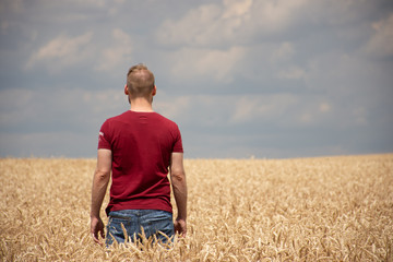 Rear View Of Man Standing At Wheat Farm Against Cloudy Sky