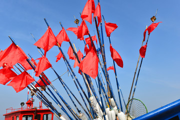 RED FISHING FLAGS ON BLUE SKY BACKGROUND