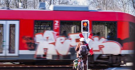 Radfahrer wartet an einem Bahnübergang vor dem Andreaskreuz auf einen vorbeifahrenden Zug