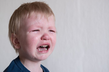 Cry. Portrait of boy. Caucasian child looks at camera. Charming boy the kid cries with tears in his eyes. an angry temper. hysterics.