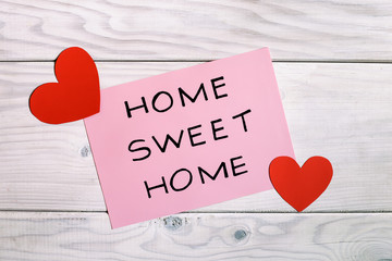 Text home sweet home with heart shapes on wooden table