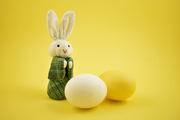 White rabbit toy stock images. Easter bunny on a yellow background. Easter rabbit with egg. Spring decoration images. Easter concept