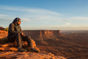 Hiker meets sunset at Grand view point in Canyonlands National park in Utah, USA