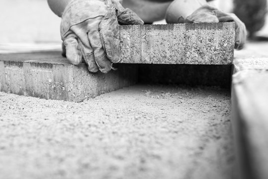 Greyscale image of workman laying a paving brick