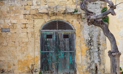 Closed old wooden door on a yellow limestone wall. Mdina, Malta