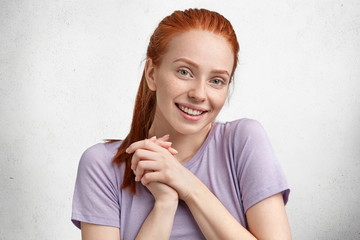 Candid shot of pleased satisfied female student, rejoices her success during studying, smiles gently at camera, has red hair tied in pony tail, dressed in casual purple t shirt, poses at studio