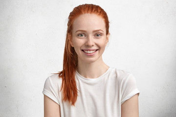 Photo of pretty satisfied ginger female, has green eyes, freckled skin, smiles pleasantly, being in high spirit as spends free time in family circle, models over white concrete wall. Positive emotions