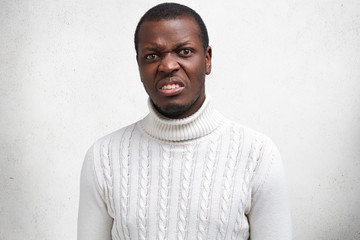 Portrait of displeased handsome young African American male has disgusting expression, frowns face, expresses negativity, dressed in casual sweater. People, ethnicity and unhappiness concept