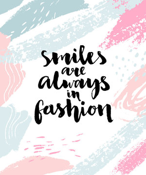 Smiles are always in fashion. Inspirational calligraphy quote on abstract brush strokes background