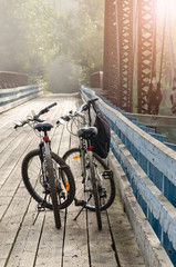 two bicycles and backpack on bridge over La Riviere-Rouge river on Corridor Aerobique bicycle trail with foggy forest and sun flare ahead in autumn early morning, Quebec, Canada, North America