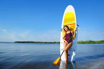 Wide picture of a woman with sup board on river background