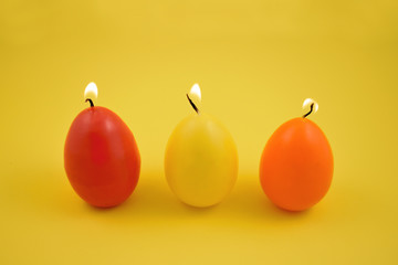 Egg candle stock images. Colored candles on a yellow background. Easter concept