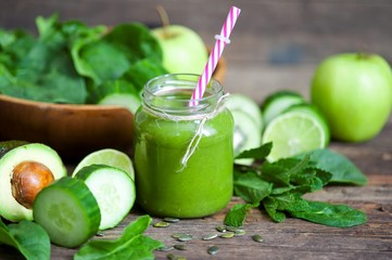 Healthy green smoothie with ingredients on wooden table