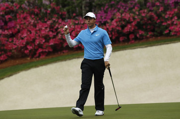 Rory McIlroy of Northern Ireland holds up his ball after saving par on the 13th during third round play of the 2018 Masters golf tournament in Augusta