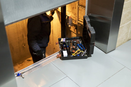 Specialist fixing or adjusting lift mechanism in elevator schaft. Regular repair, service and maintenance of elevator