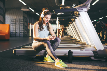 Beautiful young Caucasian girl sportswoman sitting, resting after training on treadmill against the backdrop of gym in sunny weather. Listens to music in sick white headphones,in hand holds the phone